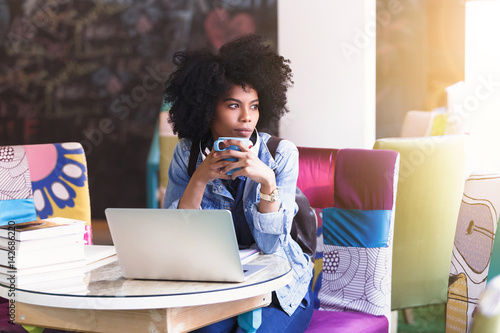 Foto  Beautiful young african american student girl with a lot of books and laptop