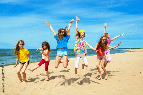 Plakat Szczęśliwi aktywni dzieci skacze na plaży