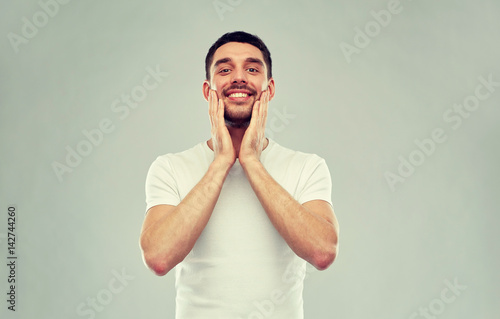 happy young man applying aftershave to face Canvas Print