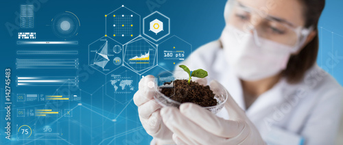 Photo scientist with plant and soil over virtual charts
