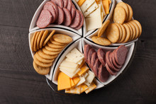 White Platter Of Crackers, Cheddar Cheese, And Sliced Meat On Dark Wooden Background Above Shot