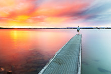 A Person Watches A Beautiful, Colourful Sunset Over The Sea From The End Of A Small Jetty.