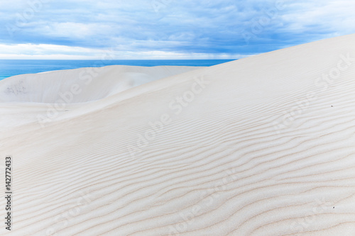 Photographie Beautiful rippled sand dunes meet the deep blue ocean under a stormy sky in this abstract seascape background