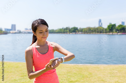 Fotografie, Obraz  Woman using smart watch at green park