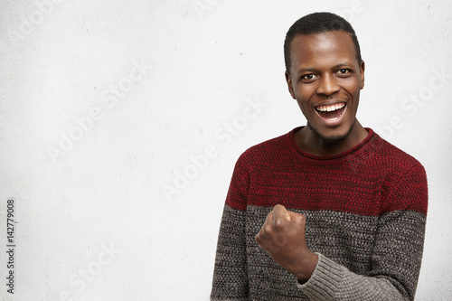 Happy successful lucky young dark-skinned man in warm