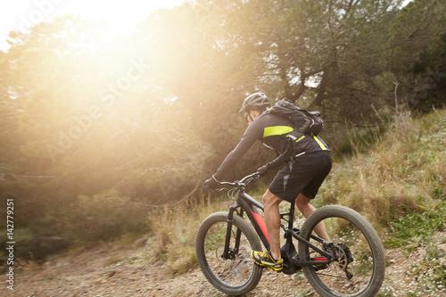 Rear shot of European professional rider in helmet, cycling