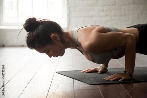 mloda-atrakcyjna-kobieta-praktykujaca-joge-stojaca-w-cwiczeniu-chaturanga-dandasana-czteroramienny-personel-pompki-lub-push-up-stanowia-wypracowanie-studio-biale-tlo-na-poddaszu-zblizenie
