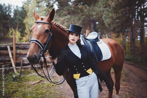 Portrait Jockey girl next to a horse, riding, concept of advertising an equestrian club, preparing for jumps. Summer. Toning.
