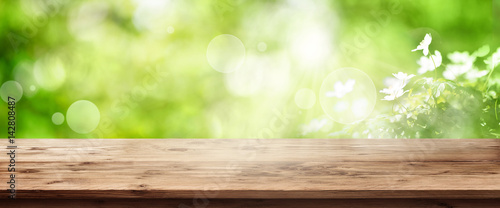 Poster Printemps Radiant green spring background with wooden table