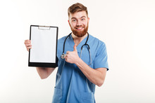 Confident Young Doctor Holding Clipboard And Giving Thumb Up