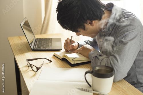 Fotografie, Obraz  机の上で仕事・勉強をする男性