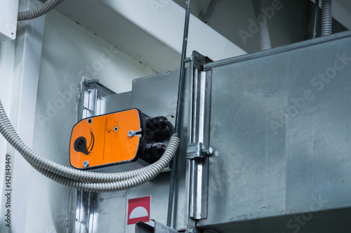 Photo Orange damper actuator installed on the ductwork of the central ventilation syst