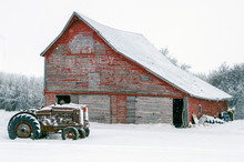 Vintage Tractors In Front Of An Old Red Barn In Snow