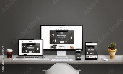Web design studio with responsive web site promotion. Computer display, laptop, tablet and smart phone mockup on office desk. Plant and coffee beside.