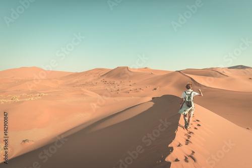 Foto  Tourist walking on the scenic dunes of Sossusvlei, Namib desert, Namib Naukluft National Park, Namibia