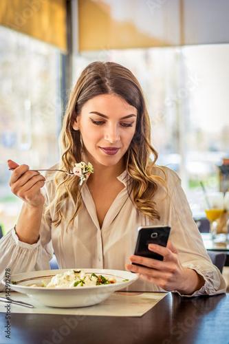 Zdjęcie XXL Młodej kobiety łasowania sałatka przy restauracją i texting na smartphone