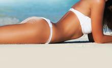 Woman Lying On Sea Beach In Bikini