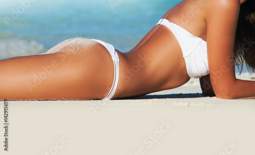 Zdjęcie XXL Kobiety lying on the beach na morzu wyrzucać na brzeg w bikini