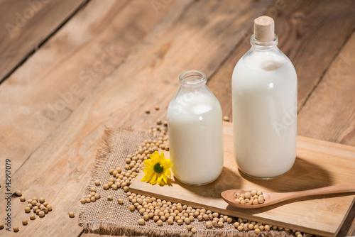 Foto op Aluminium Milkshake A bottle of soy milk or soya milk and soy beans on wooden table.