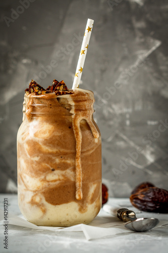 Photo Chocolate smoothie in glass jar with a banana, dates and sweets