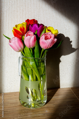 Papiers peints Narcisse A bouquet of tulips in the sun is on a table in a vase