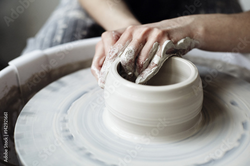 Fototapeta The woman's hands close up, the masterful studio of ceramics works with clay on