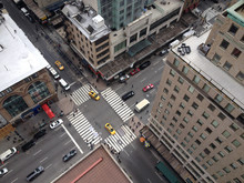 Bird's Eye View Of 5th Avenue From Tall New York City Skyscraper.  Busy Manhattan Intersection.  New York Yellow Taxis And People Crossing Busy City Intersection.  Urban New York Life. Looking Down.