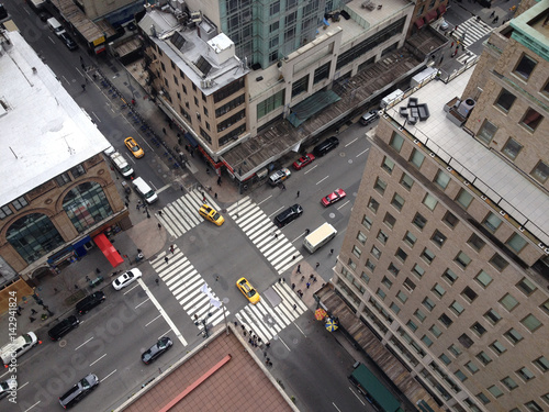 Foto op Plexiglas New York TAXI Bird's eye view of 5th Avenue from tall New York City skyscraper. Busy Manhattan intersection. New York yellow taxis and people crossing busy city intersection. Urban New York life. Looking down.