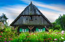 Garden With Flowers In Front Of The Old, Wooden Hut.