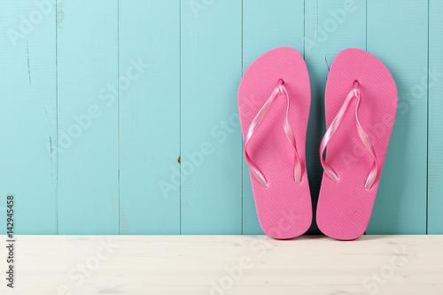 Pink flip flops on wooden background