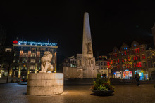 Some Tourists Watching The Monument On The Dam Square At Night, Amsterdam, The Netherlands