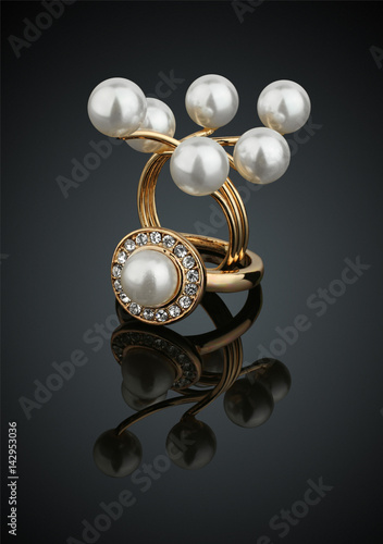 Two jewelry rings with pearls on black background with reflection