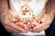 Leinwandbild Motiv Family holding house in hands