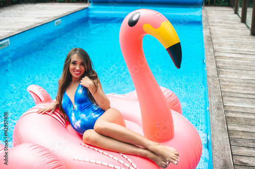 36b6e3be90f89 Beautiful pregnant woman, wearing swimsuit, lying on a pink flamingo air mattress  in a pool of blue water, summer
