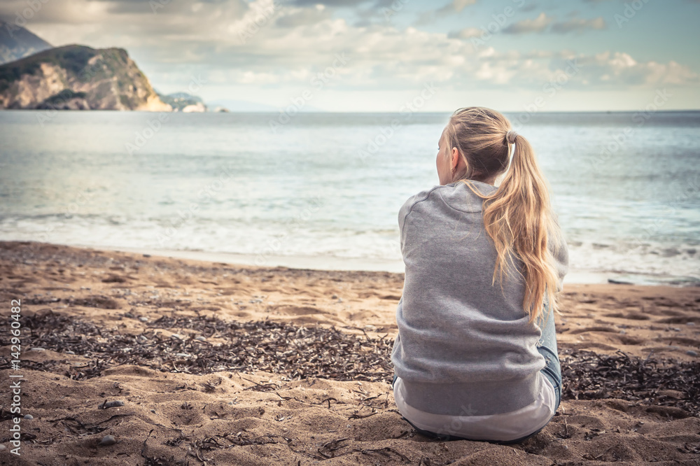 Fototapety, obrazy: Pensive lonely young woman sitting on beach hugging her knees and looking into the distance with hope