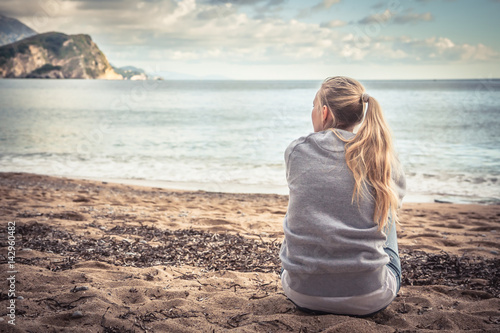 Fotografía  Pensive lonely young woman sitting on beach hugging her knees and looking into t