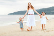 Happy family mother and children on beach by sea in summer