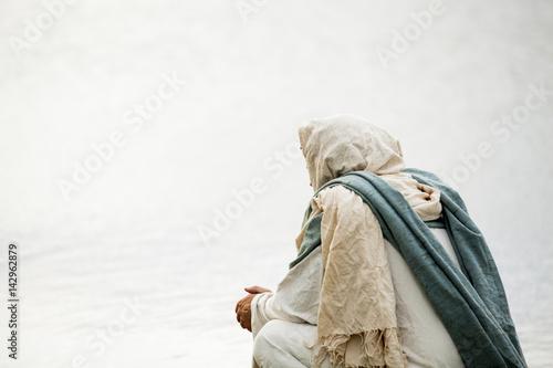 Fotografía Jesus kneeling in prayer next to a body of water