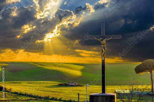 Foto  Jesus Christ on the cross by the road in the fields at sunset, with drammatic clouds and sun rays on the sky