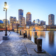 The Boston Harbor and Financial District in Boston, MA, USA at sunset.