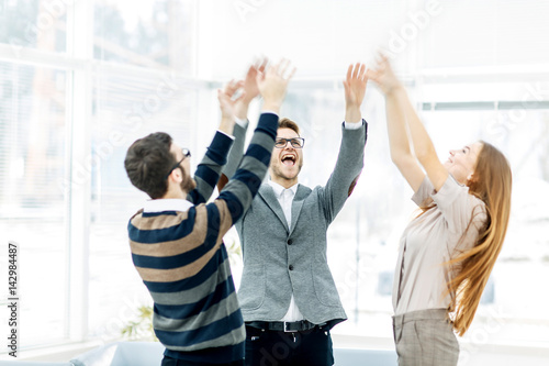 Fotografie, Obraz  concept of victory - the jubilant business team standing in a circle, hands up in rejoice success
