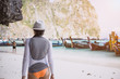 The photo was made on the islands Phi - Phi in the province of Krabi, in Thailand. The girl is walking along the shore during the day. In the photo you can see boats and rocks of the island.