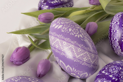 Photo  purple eastern egg on white cloth with purple tulip