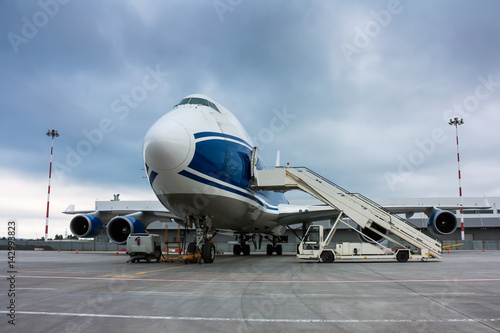 Foto op Aluminium Luchthaven Cargo wide body plane and aircraft passenger loader near terminal