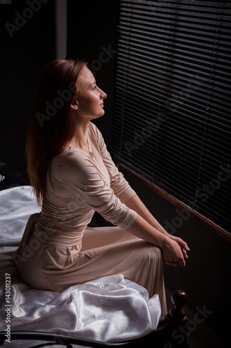 Beautiful young woman in dark interior 08192cb48