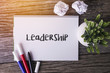 Leadership word with Notepad and green plant on wooden background.