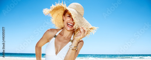 Smiling woman in swimsuit hiding in big straw hat at sandy beach