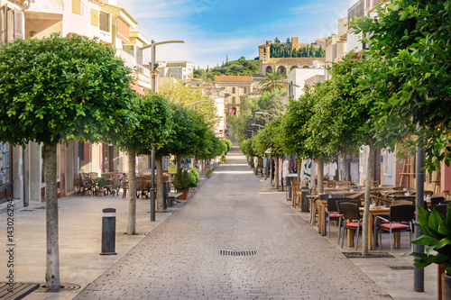 Beautiful tree-lined long street in Arta, Mallorca, in the background is Church and historic buildings. Beautiful day for walk through this amazing city.