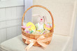 Easter basket with sweets and presents on beige chair