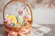 Easter basket with toy and sweets on light background